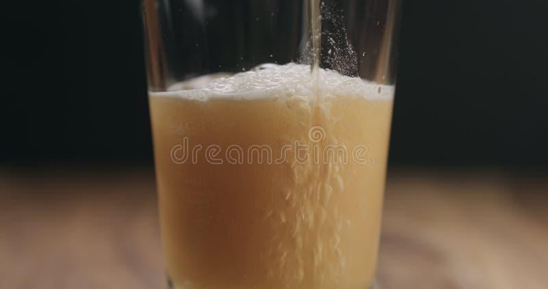 Zbliżenie niecka ale piwo nalewa w szkło na drewnianym stole fotografia stock