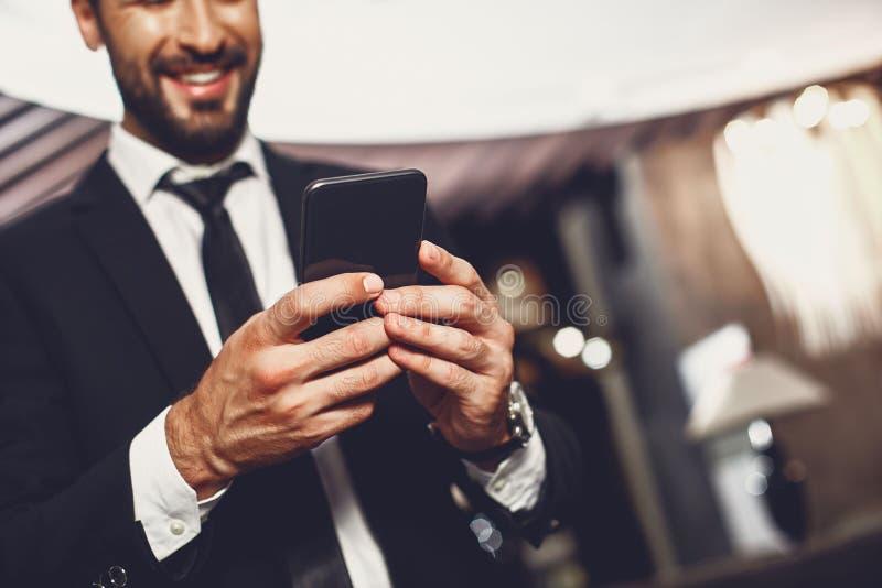 Zbliżenie nowoczesnego smartfona w rÄ™kach uÅ›miechniÄ™tego czÅ'owieka zdjęcie stock