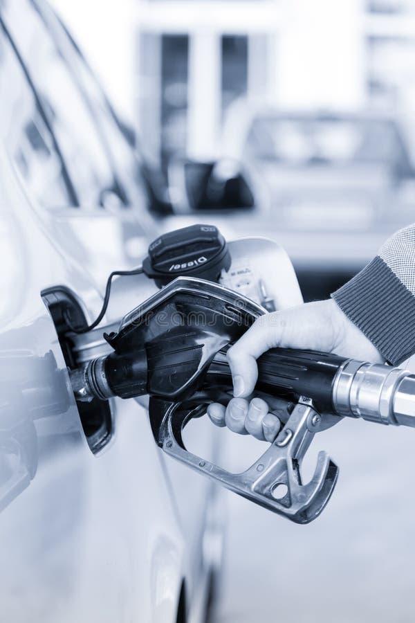 Zbliżenie obsługuje rękę pompuje benzyny paliwo w samochodzie przy benzynową stacją zdjęcie stock