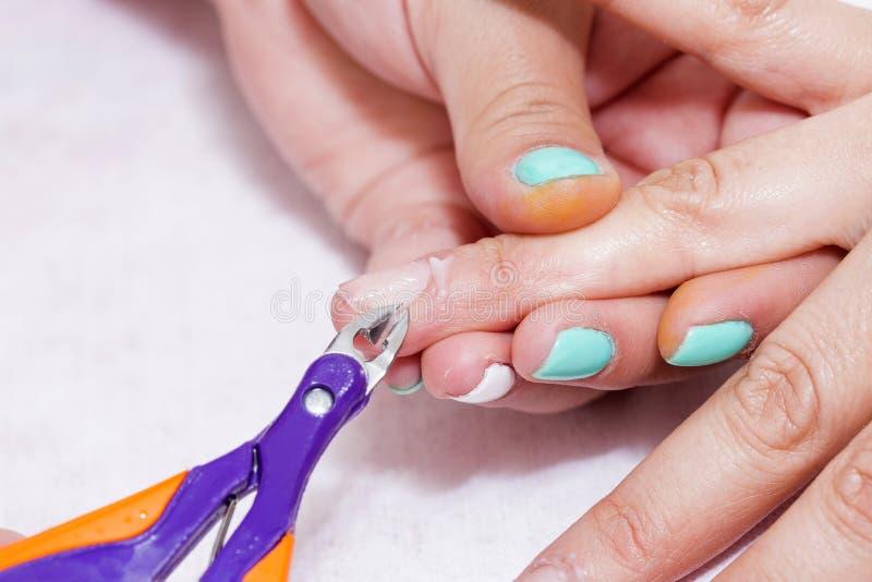 Zbliżenie palca gwoździa opieka manicure'u specjalistą w piękno salonie Manicurzysty jasnego oskórka fachowi nożyce dla manicure' zdjęcie royalty free