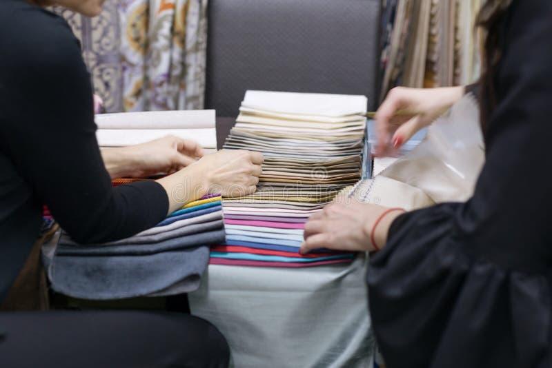 Zbliżenie paleta z tkaninami, kobiety wręcza wzruszające stubarwne próbki, tła wewnętrzne tkaniny dla zasłoien sklep i obrazy stock