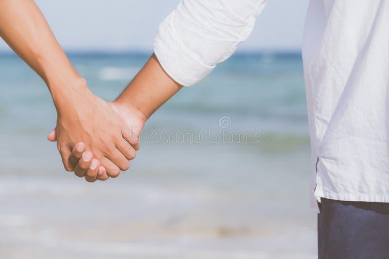 Zbliżenie pary azjatykci homoseksualny mienie wręcza na plaży z wpólnie relaksuje i czas wolny w lecie zdjęcia stock