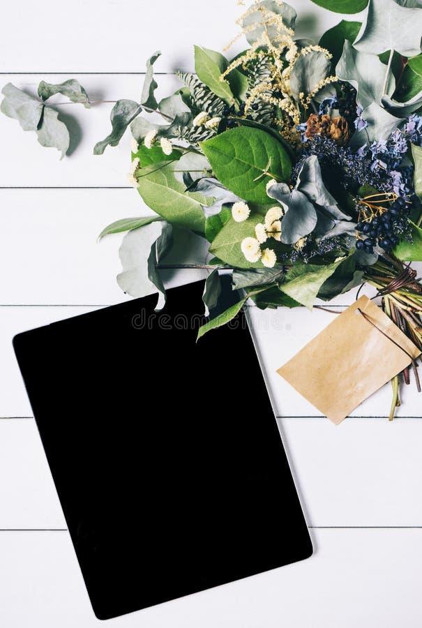 Zbliżenie pastylka z pustym pustego ekranu monitorem z bukietem kwiaty na bielu stołu tle z naturalnym drewnianym rocznikiem fotografia royalty free