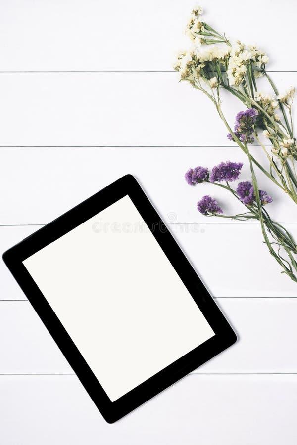 Zbliżenie pastylka z pustym pustego ekranu monitorem z bukietem kwiaty na bielu stołu tle z naturalnym drewnianym rocznikiem zdjęcie royalty free