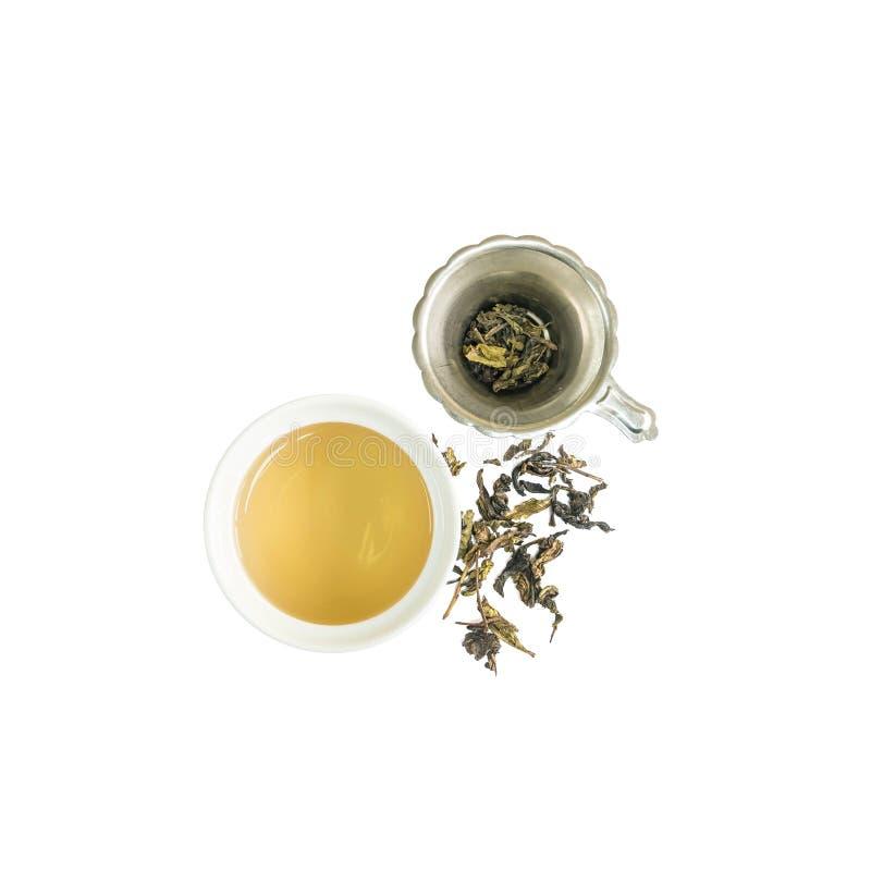 Zbliżenie piękna ceramiczna filiżanka herbata z brown herbatą i suszący herbaciany urlop w herbacianym durszlaku odizolowywającym obraz stock