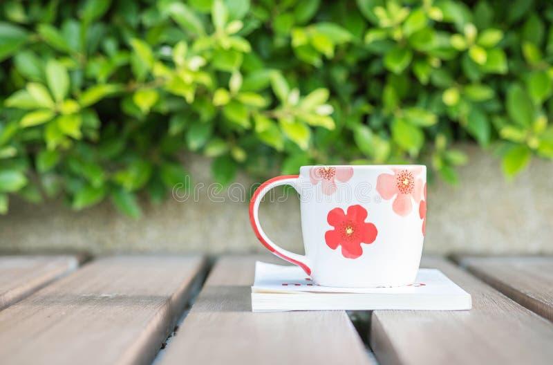 Zbliżenie piękna filiżanka kawy na białej książce na zamazanym drewnianym stole i zielonej roślinie w ogrodowym textured tle, rel zdjęcie stock