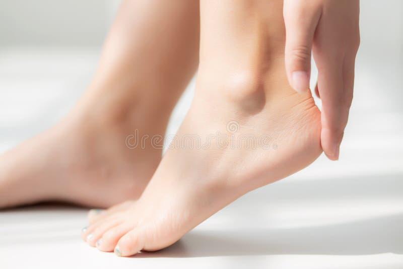 Zbliżenie piękna młoda azjatykcia kobieta stosuje śmietankę i płukankę na stopie suchej na łóżku zdjęcie stock