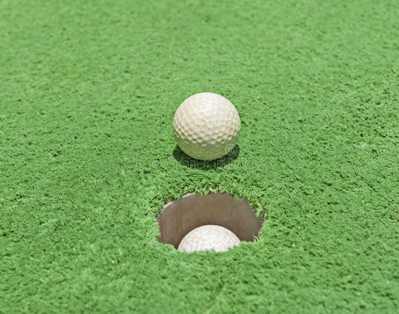 Zbliżenie piłka golfowa dziurą na zielonym astroturf zdjęcia stock