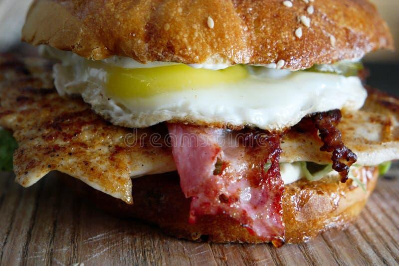 Zbliżenie piec na grillu hamburger stufed z kurczaka mięsem, fryed jajkiem i backon, zdjęcia royalty free