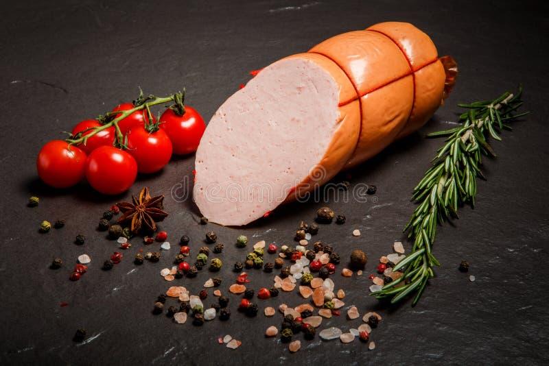 Zbliżenie połówka pokrojona gotowana kiełbasa słuzyć z pikantność i rozmarynami zdjęcie stock