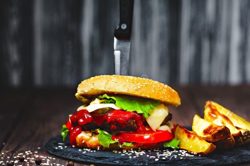 Zbliżenie podlewanie, wyśmienicie domowej roboty hamburgery z nożem wtykającym na kamieniu wsiada drewniany tło zmrok obrazy stock