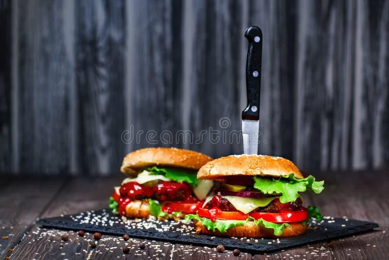 Zbliżenie podlewanie, wyśmienicie domowej roboty hamburgery z nożem wtykającym na kamieniu wsiada drewniany tło zmrok zdjęcia royalty free