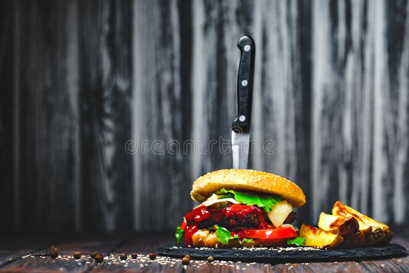 Zbliżenie podlewanie, wyśmienicie domowej roboty hamburgery z nożem wtykającym na kamieniu wsiada drewniany tło zmrok fotografia royalty free