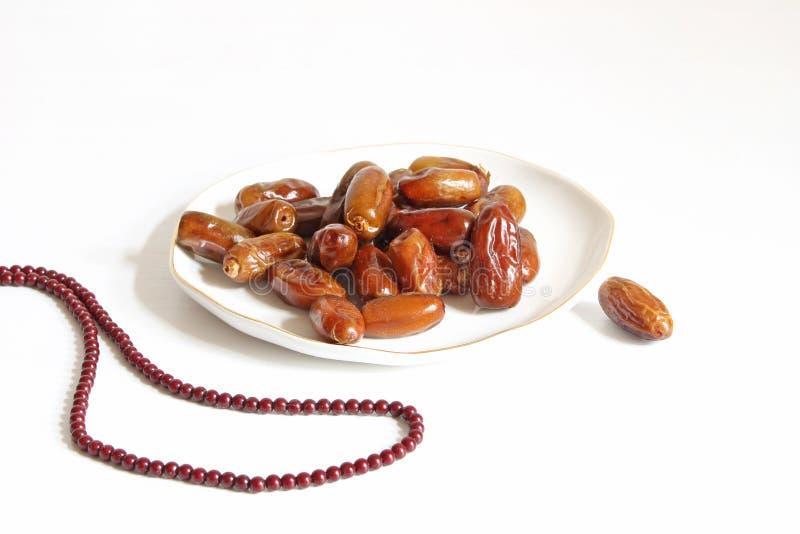 Zbliżenie porcelana talerz z daktylowymi owoc i modlitewnymi koralikami na białym stole Kartka z pozdrowieniami dla iftar i Ramad fotografia royalty free