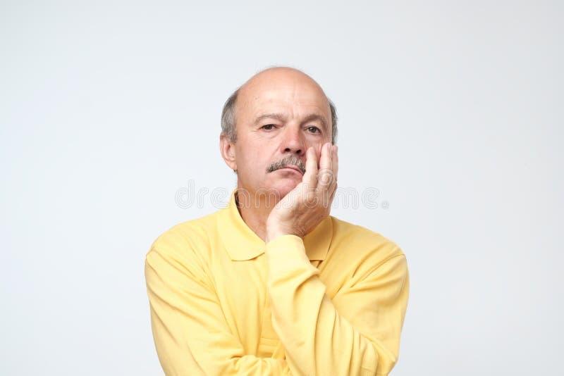 Zbliżenie portret śpiący dojrzały mężczyzna w żółtej koszulce, śmieszny facet umieszcza głowę na ręce, nieszczęśliwa patrzeje kam zdjęcie royalty free