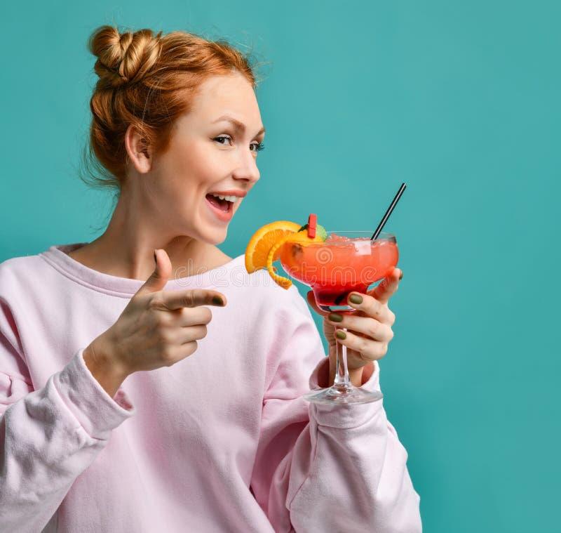 Zbliżenie portret barman kobieta z truskawkowym margarita koktajlem w ręce w czerwony szczęśliwy ono uśmiecha się na błękicie obrazy royalty free