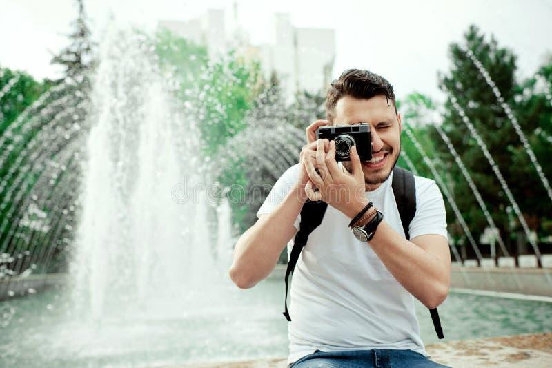 Zbliżenie portret bierze fotografię w miasto parku przystojny młody człowiek Elegancka chłopiec w białym tshirt z bagpack b fotografia royalty free