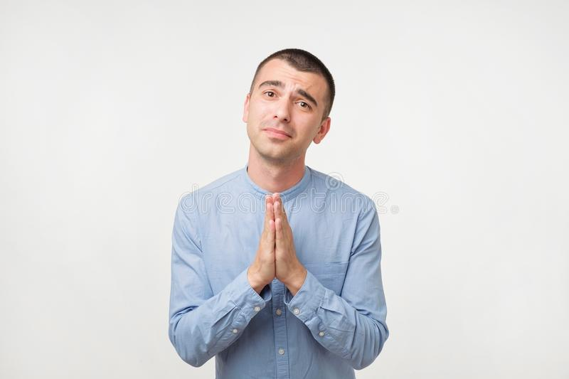 Zbliżenie portret desperacki młody człowiek w błękitny seans spinać koszula rękach, pytać dla pomocy lub wymówki fotografia royalty free