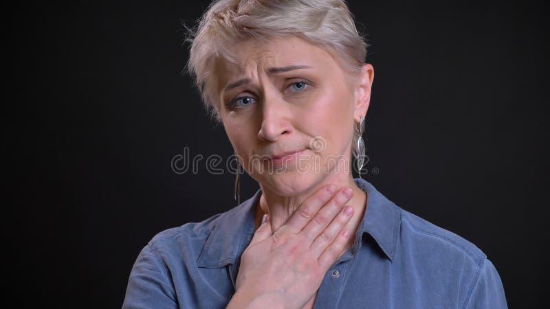 Zbliżenie portret dorosła atrakcyjna caucasian kobieta ma chorego gardło i jest chory podczas gdy patrzejący kamerę z obrazy royalty free