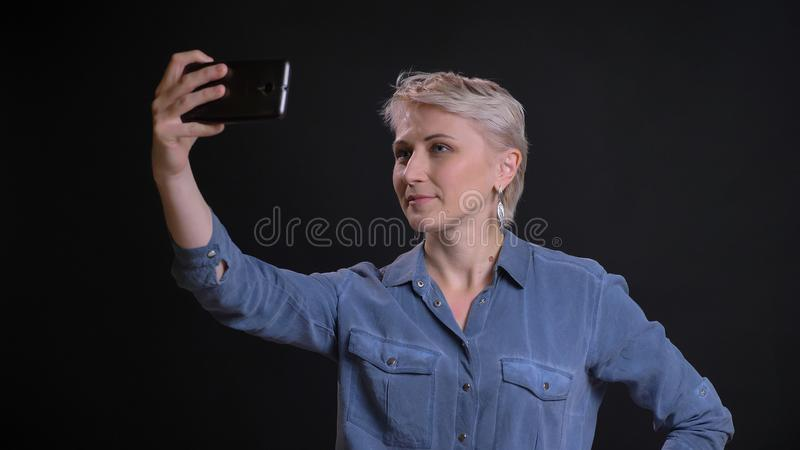 Zbliżenie portret dorosła caucasian kobieta z krótkim blondynka włosy bierze selfies na telefonie z tłem odizolowywającym zdjęcia royalty free