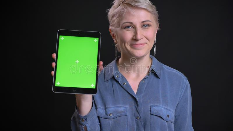 Zbliżenie portret dorosła uśmiechnięta caucasian kobieta z krótkim blondynka włosy używać pastylkę i pokazywać zieleń ekran zdjęcie royalty free