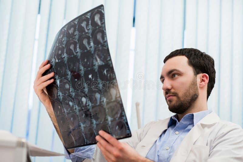 Zbliżenie portret intelektualny mężczyzna opieki zdrowotnej personel z białym labcoat, patrzeje móżdżkowego promieniowania rentge obrazy royalty free