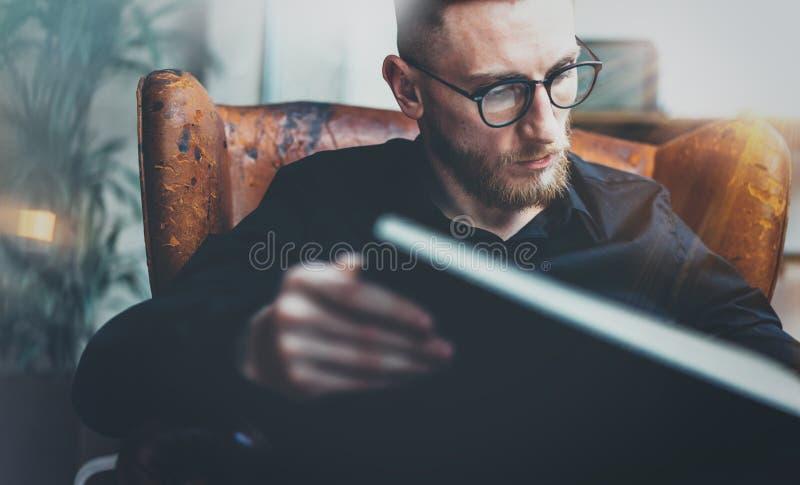 Zbliżenie portret inteligentnego biznesmena czytelnicza książka podczas gdy siedzący w rocznika krześle Młody brodaty mężczyzna r fotografia royalty free