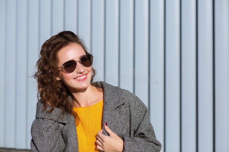 Zbliżenie portret jest ubranym okulary przeciwsłonecznych i żakiet pozytywna dziewczyna, pozuje blisko żaluzji Przestrzeń dla tek zdjęcie stock