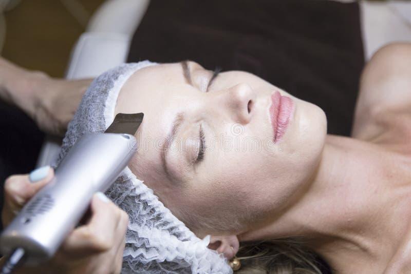 Zbliżenie portret kobieta i ręka z kosmetycznym podnośnym przyrządem dotyka jej twarz obraz stock