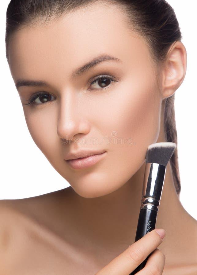 Zbliżenie portret kobieta stosuje suchą kosmetyczną tonalną podstawę na twarzy używać makeup muśnięcie fotografia stock