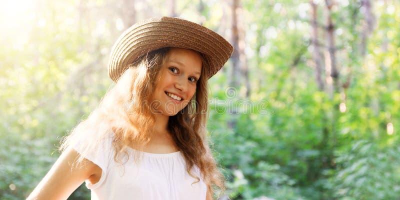 Zbliżenie portret młoda longhair dziewczyna w słomianym kapeluszu w jaskrawym świetle słonecznym przeciw zamazanemu natury tłu fotografia royalty free
