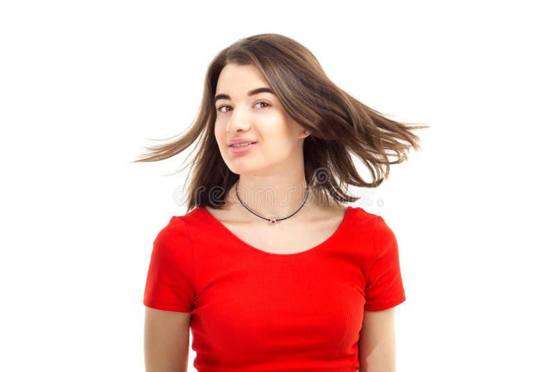 Zbliżenie portret młoda szczęśliwa uśmiechnięta dziewczyna w czerwonej koszulce, wiatr dmucha jej włosy przeciw białemu tłu zdjęcia stock