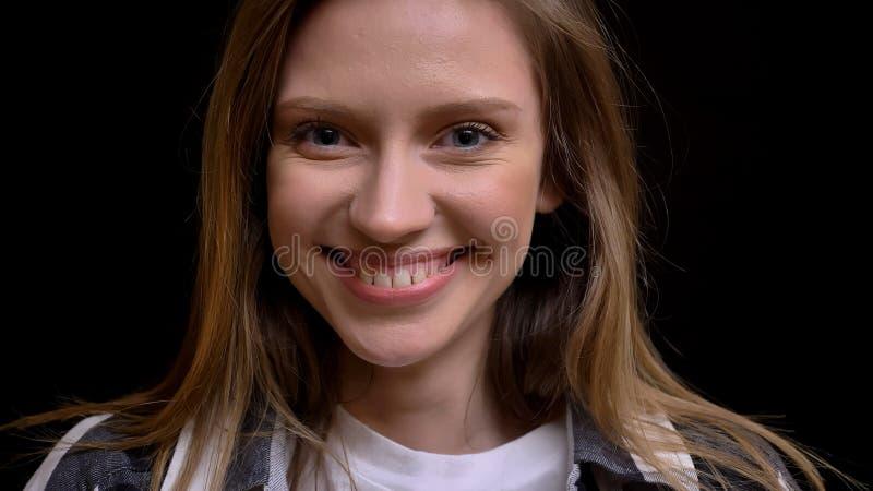 Zbliżenie portret młody powabny caucasian żeński patrzeć prosto przy kamerą i ono uśmiecha się z jej zębami zdjęcia royalty free