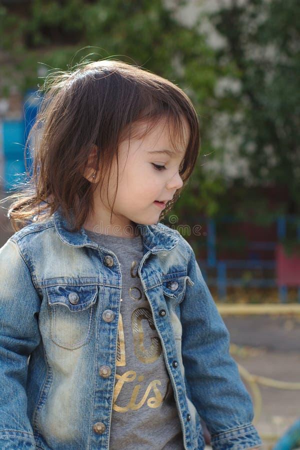 zbliżenie portret mała śliczna emocjonalna dziewczyna z pigtails w drelichowej kurtce obrazy royalty free