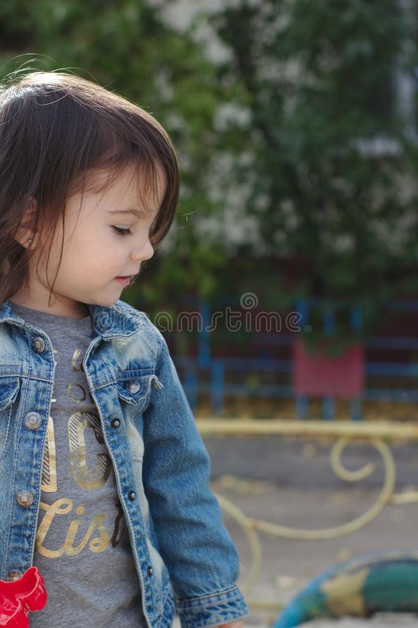 zbliżenie portret mała śliczna emocjonalna dziewczyna z pigtails w drelichowej kurtce zdjęcie stock