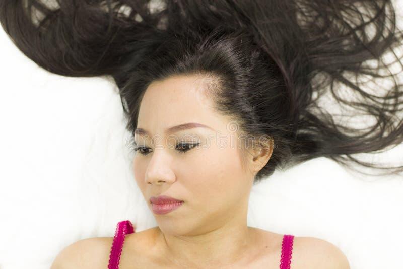 Zbliżenie portret markotne azjatykcie kobiety kłama na ziemi z czarny długie włosy postępować spęczenie, nieszczęśliwego obraz royalty free