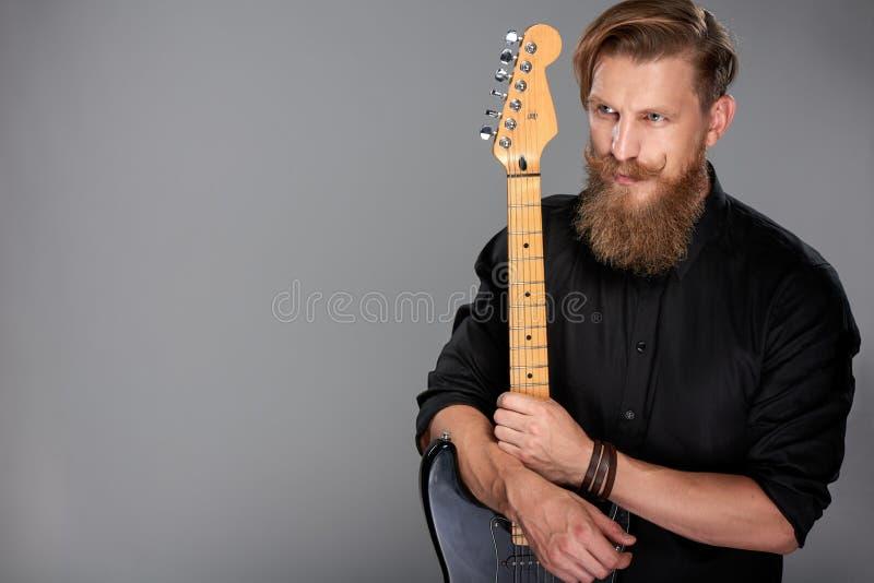 Zbliżenie portret modnisia mężczyzna z gitarą obraz stock
