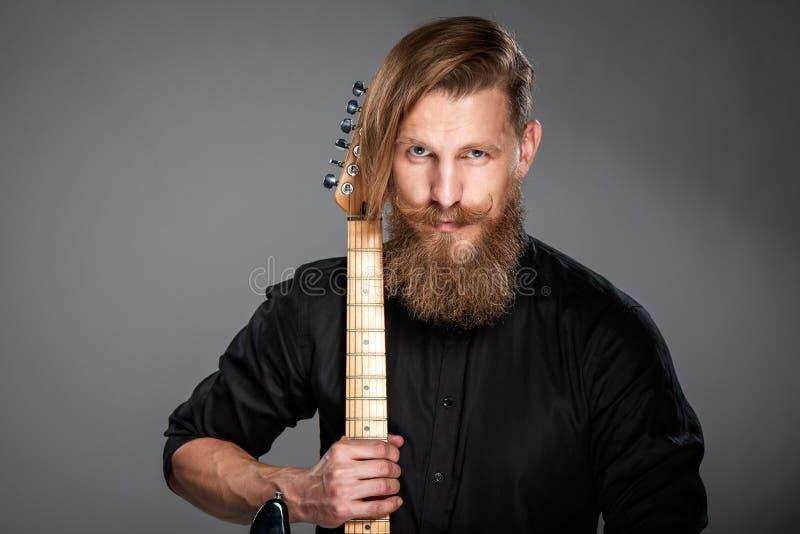 Zbliżenie portret modnisia mężczyzna z gitarą fotografia royalty free