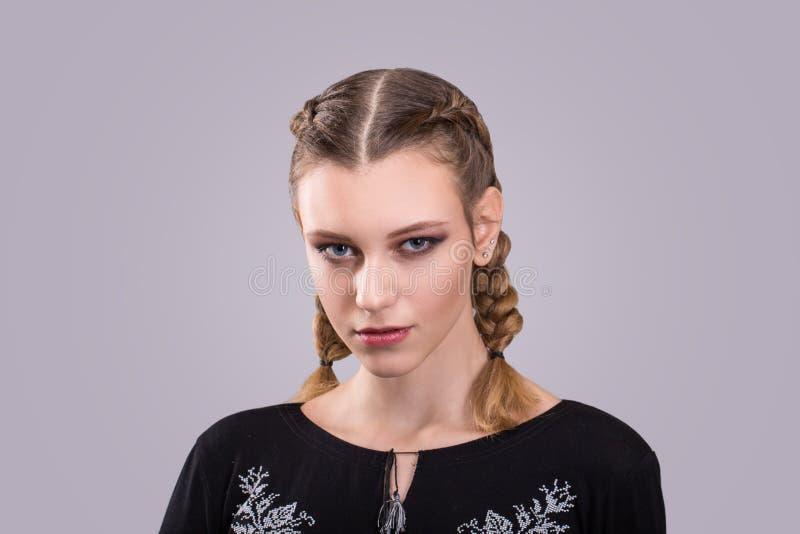 Zbliżenie portret nastoletnia dziewczyna stoi przed a i szarym tłem z galonowymi pigtails fotografia royalty free