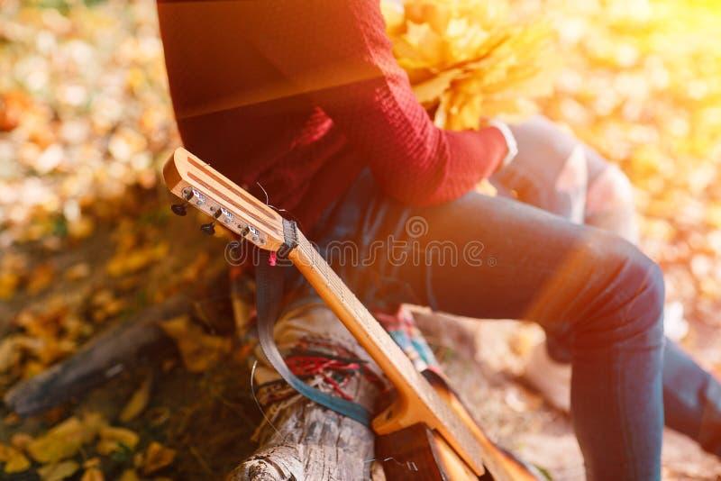 Zbliżenie portret pary obsiadanie z gitarą blisko ogniska w lesie zdjęcia stock