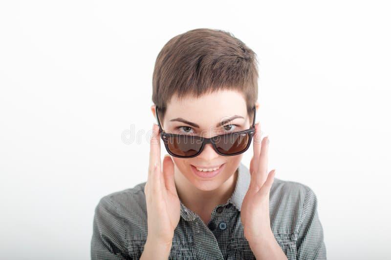 Zbliżenie portret piękna młoda uśmiechnięta kobieta patrzeje nad okularami przeciwsłonecznymi na białym tle z ciemnym krótkim wło fotografia royalty free
