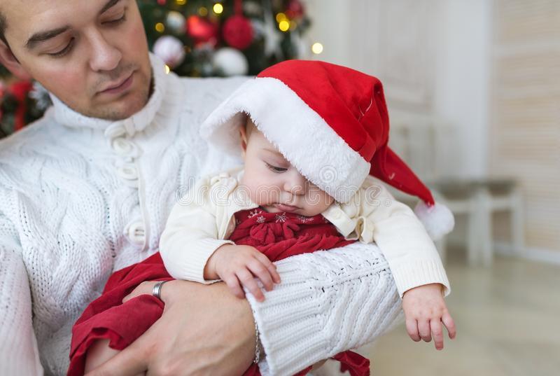 Zbliżenie portret potomstwa ojcuje w biel ubraniach trzyma ich nowonarodzonego dziecka przeciw dekorującej mrugliwej choince fotografia royalty free