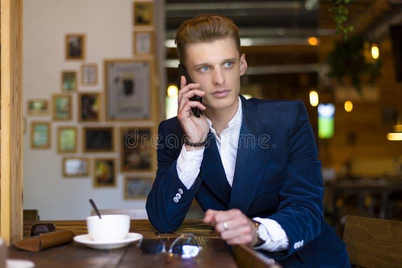 Zbliżenie portret poważny przystojny mężczyzna opowiada na smartphone i obsiadaniu przy stołem w kawiarni Frontowy widok obraz stock