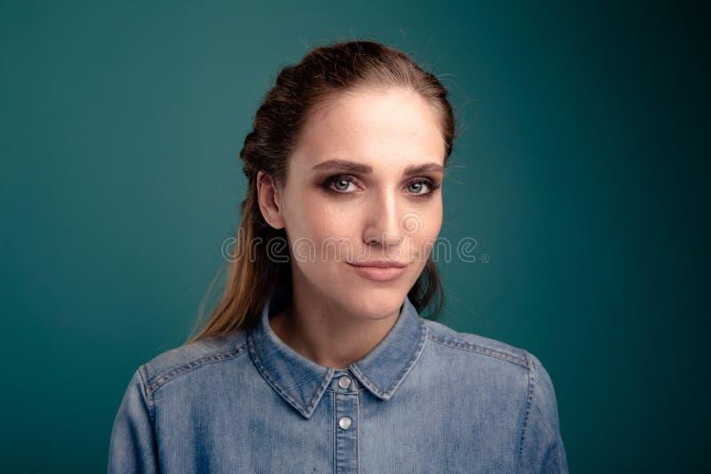 Zbliżenie portret pozuje w studiu odizolowywającym nad błękitnym tłem ładna młoda kobieta fotografia stock
