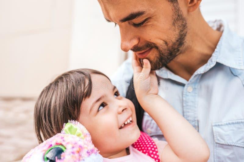 Zbliżenie portret przystojni szczęśliwi potomstwa ojcuje uścisk po preschool dnia jego córka Śliczna mała dziewczynka patrzeje je obrazy royalty free