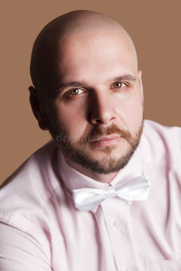 Zbliżenie portret przystojny brodaty łysy mężczyzna w świetle - różowy shir zdjęcia stock
