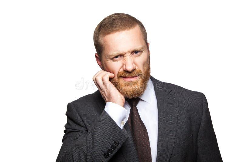 Zbli?enie portret rozwa?ny zmieszany przystojny biznesmen z brod? w czarnego kostiumu trwanie chrobocie jego twarz i patrze? obraz stock