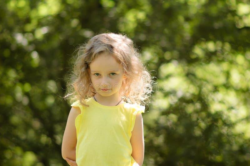 Zbliżenie portret skeptical mała dziewczynka patrzeje podejrzliwie, skeptical, półuśmiech, ironicznie zielony portret obrazy stock