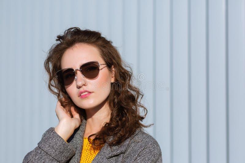 Zbliżenie portret splendoru modnisia wzorcowi jest ubranym okulary przeciwsłoneczni i żakiet, pozuje blisko żaluzji Przestrzeń dl zdjęcia royalty free