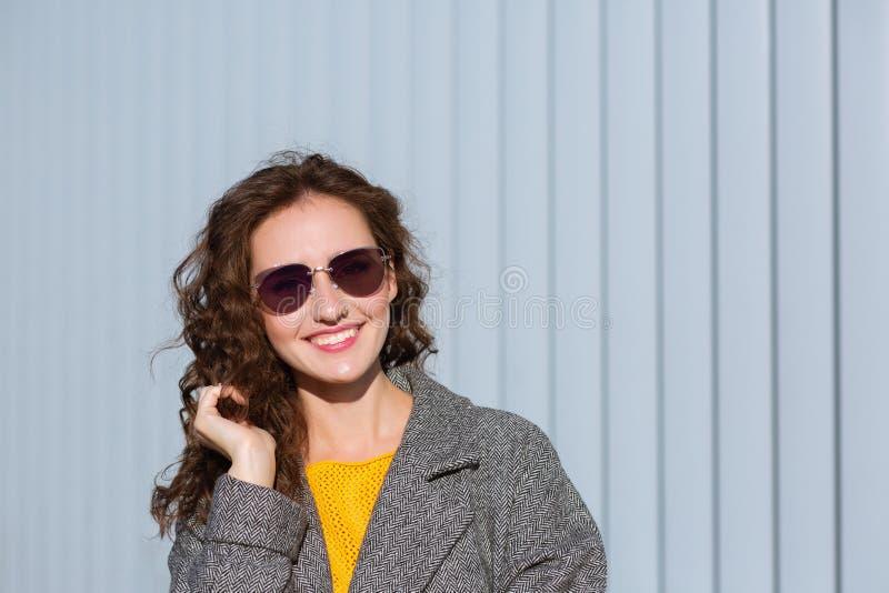 Zbliżenie portret szczęśliwa modniś dziewczyna jest ubranym okulary przeciwsłonecznych i żakiet, pozuje blisko żaluzji Przestrzeń fotografia royalty free